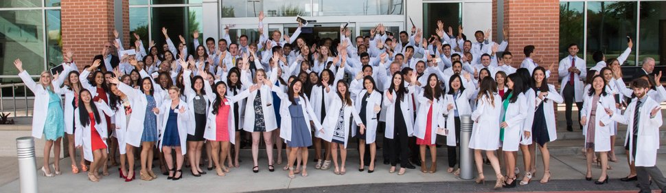 103 dental students in white coats, group photo on steps of School of Dentistry