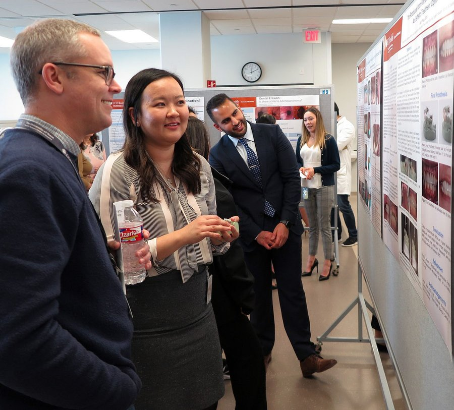 Faculty, residents and students discussing research posters.