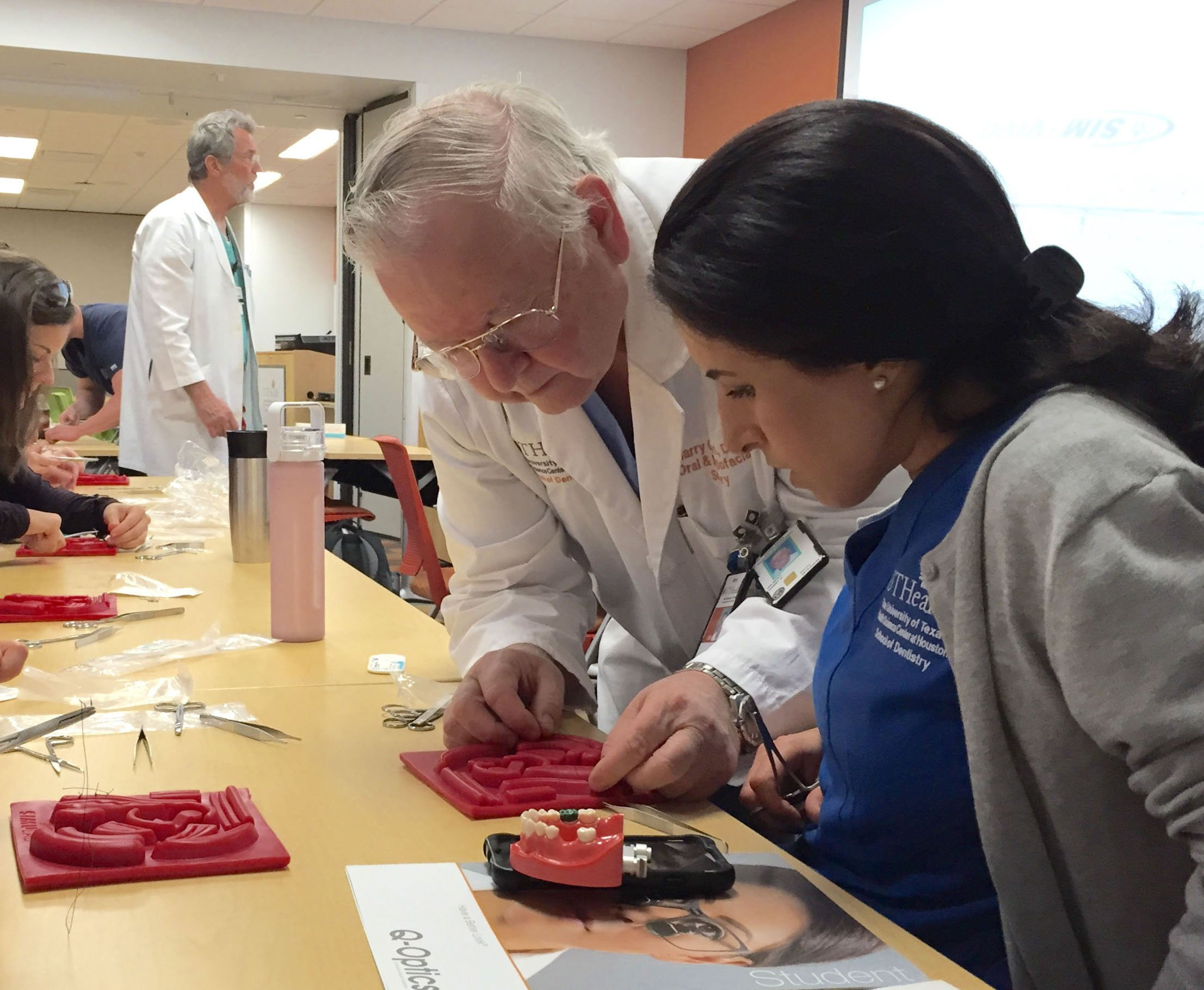 Dr. Harry Gilbert shows a dental student how to suture gums.