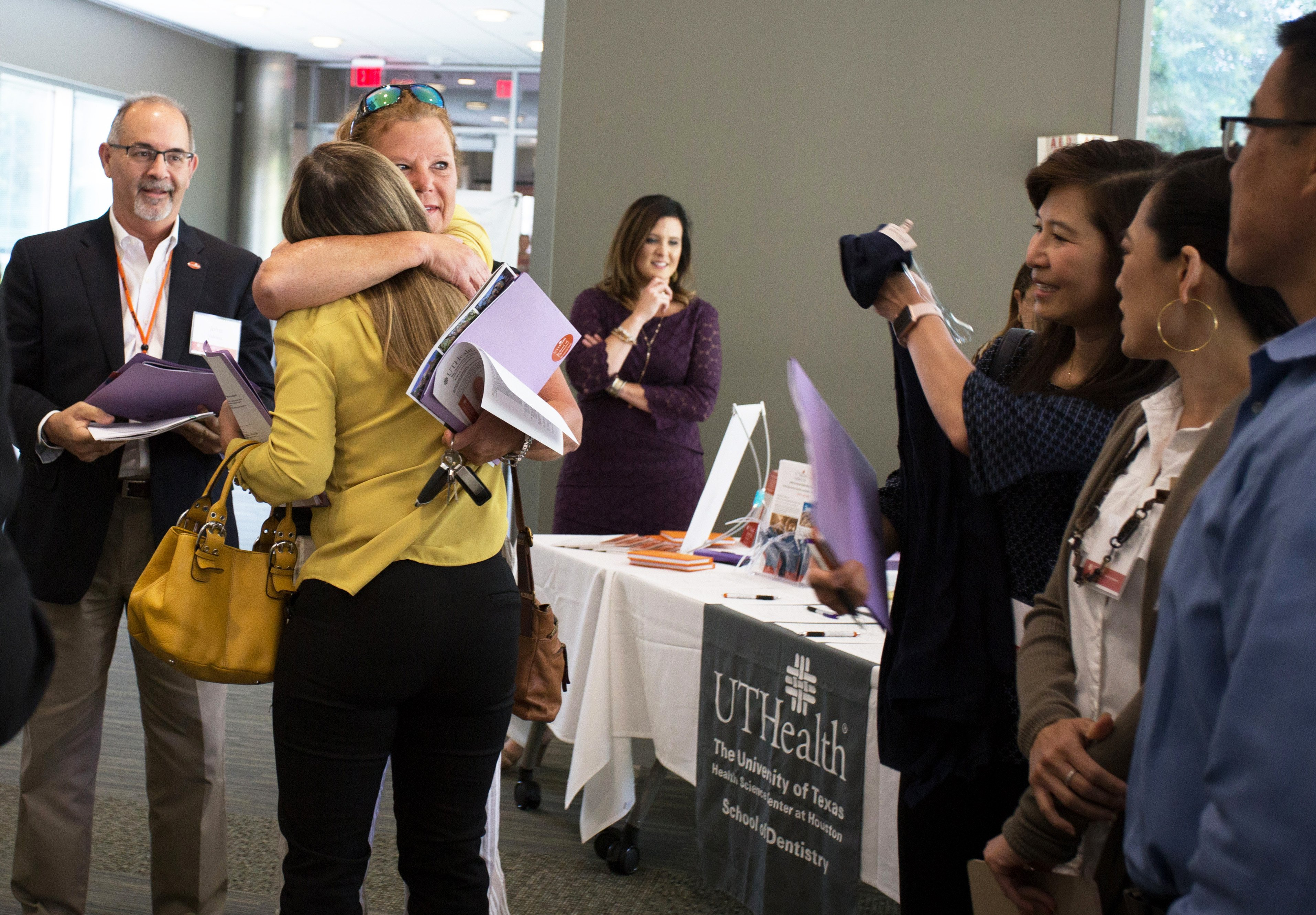 Nina Leifeste, DDS '88, GPR '89 hugs a colleague at the General Practice Residency program's 30th anniversary reunion at the Cooley Center. Dean John Valenza, DDS '81 (left) was the program's founding director in 1988.