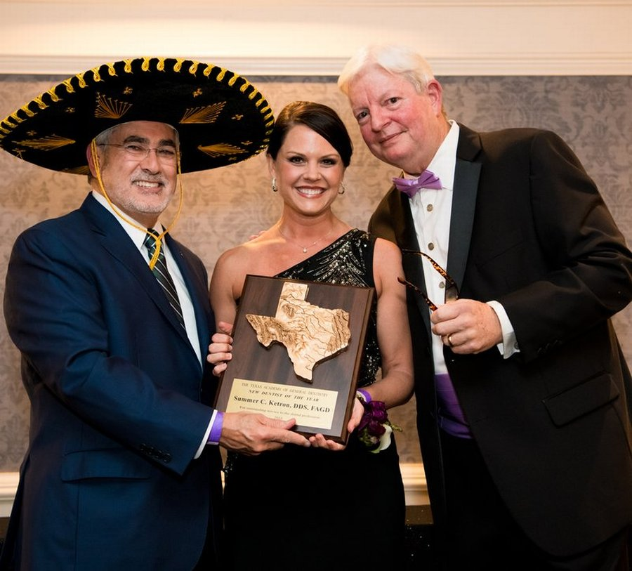Wearing a sombrero, the AGD president (left) presents the trophy for Texas New Dentist of the Year to Dr. Summer Ketron (center) as the TAGD past president looks on.