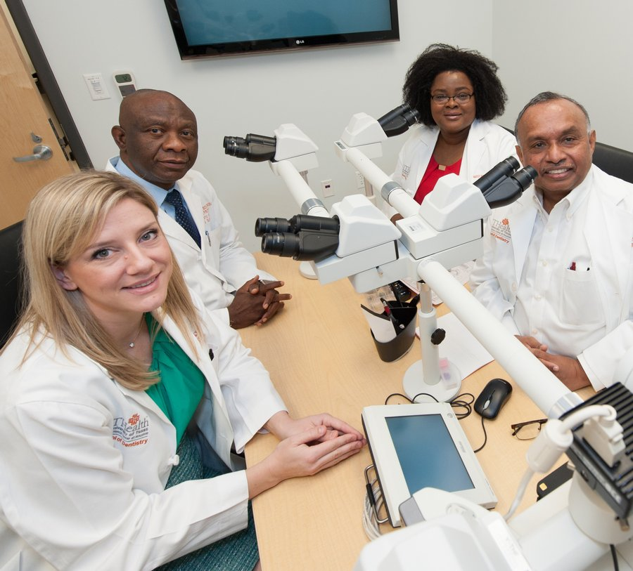 Oral and maxillofacial pathology faculty members at UTHealth School of Dentistry sit at a table looking through a four-head microscope.