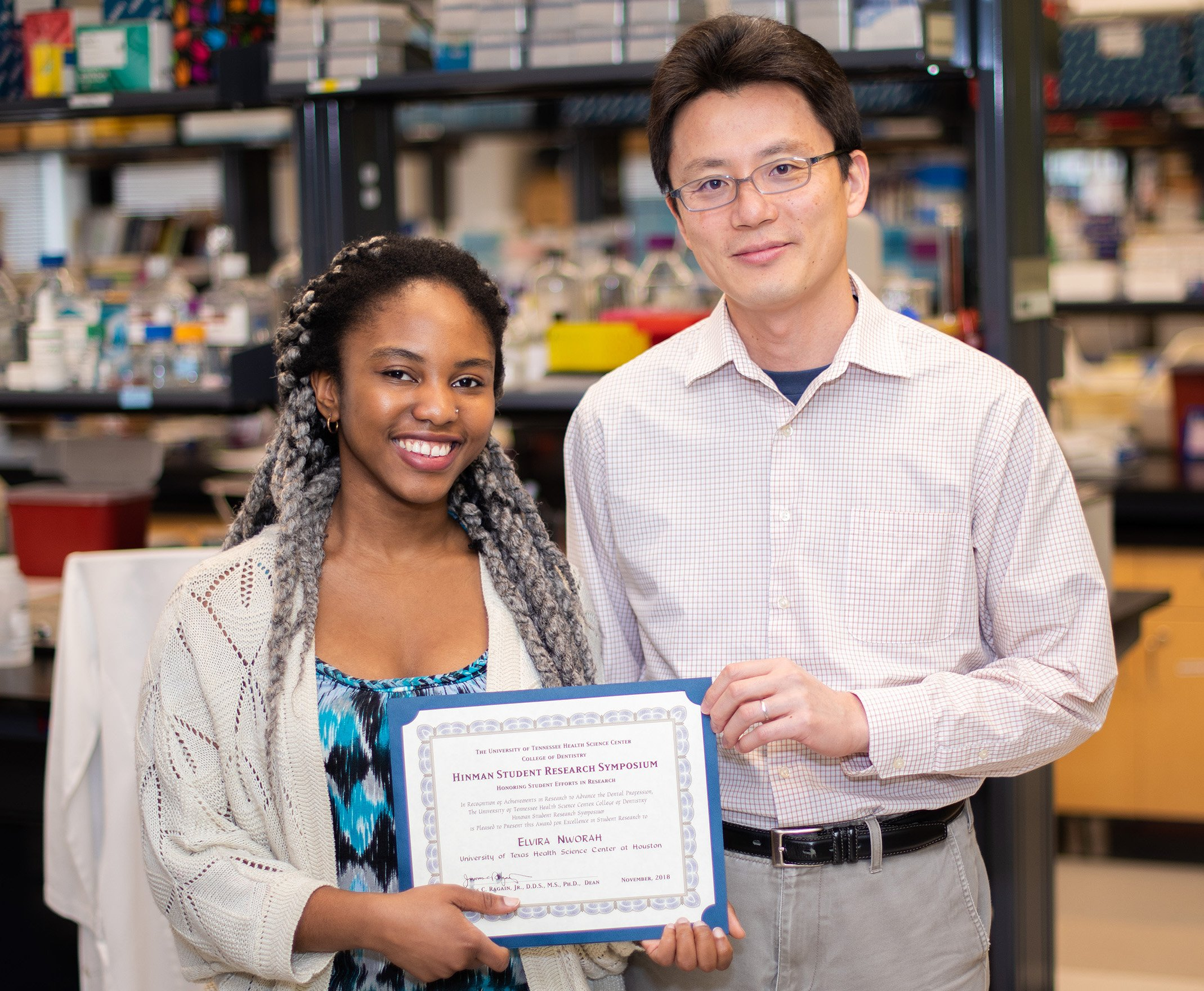 UTHealth dental student Elvira Nworah holds the NSRG Award she won at the Hinman Student Research Symposium. With her is Associate Professor Junichi Iwata, DDS, PhD.