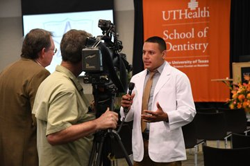 male student in white coat being interviewed on camera for univision