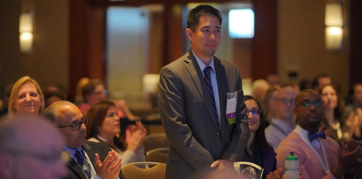 Dr. Ryan Quock stands as the audience applauds the announcement that he is the new chair-elect of the ADEA Board of Directors.