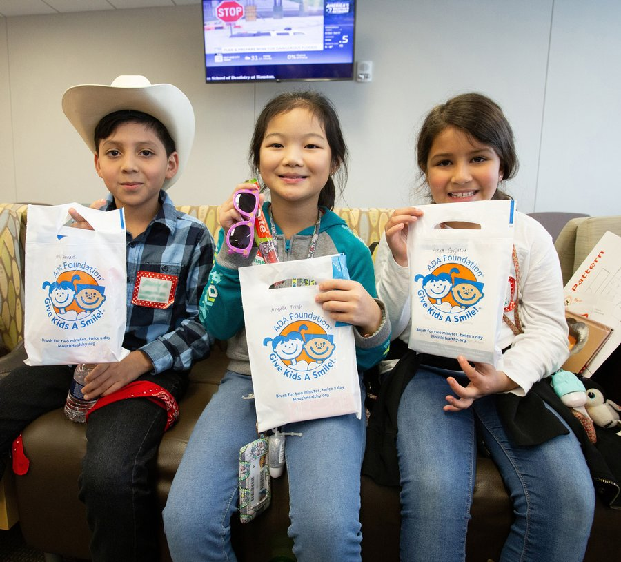 Three children in western attire sit on a couch and hold up bags that say Give Kids A Smile.