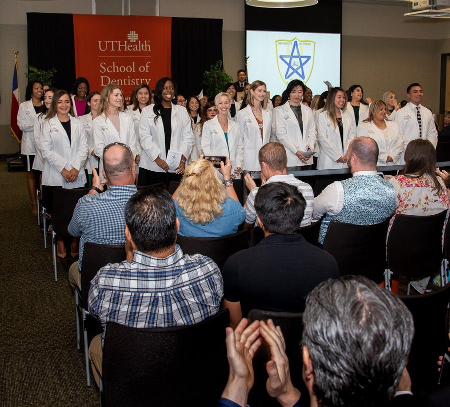 After receiving their white coats, dental hygiene students turn to face an applauding audience of family and friends.