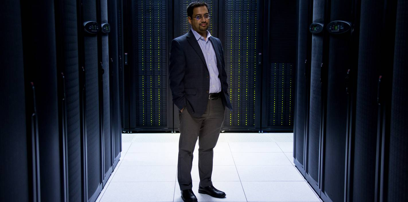 Dr. Muhammad Walji standing among the servers that host the BigMouth Dental Data Repository.