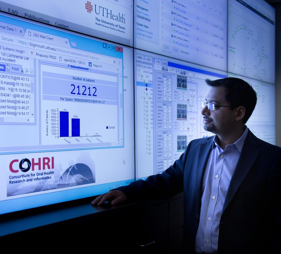 Dr. Muhammad Walji stands before a wall of computer screens, including one for COHRI.
