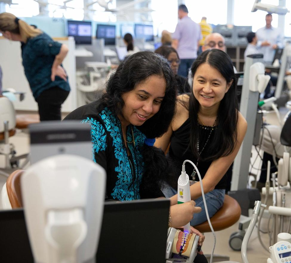 School of Dentistry faculty members Gargi Mukherji, DDS, (left) and Sudarat Kiat-amnuay, DDS, MS, practice taking digital impressions in the school's Clinical Simulation Center.