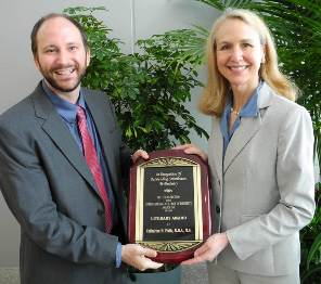 Nathan Carlin, PhD and Catherine Flaitz, DDS, MS, with the award she won for an article they wrote together.