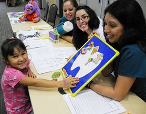 Dental hygiene students (from left) Violeta Ayer, Ami Sanchez and Veronica Cordon teach Maddison Palencia, 4, of Houston about foods that stick to teeth.