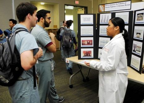 Dr. Michelle Aguilos explains her research on dental implants to dental students Dustin Adamek (left) and Tamir Anver.