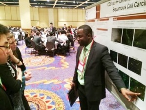 Third-year dental student Arsene Hanana explains his research poster at the American Student Dental Association's annual meeting.