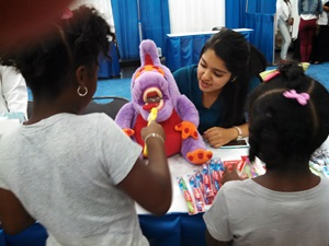 Dental hygiene student Elizabeth Castillo works with a puppet to teach toothbrushing at the Texas Black Expo Health Fair.