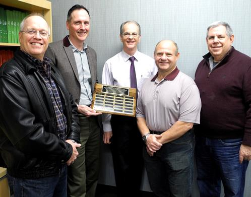 Dr. Jeffery Hoover (center) with his fellow HEAF members and a plaque honoring his service as president for 2012-13.  From left are Dr. Tod Bruchmiller; incoming president Dr. Chris L. Coleman; Hoover; Dr. Kim Freeman and Dr. Sam Dorn. The plaque is on permanent display in the Department of Endodontics. Photo by Rhonda Whitmeyer.