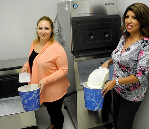 UTSD staffers Krystal Conde (left) and Melinda Polanco load up on crushed and cubed ice available from ice machines on the third floor.