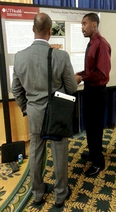 Dental student Nick Ayoade (right) answers questions about his research at the 101st NDA Annual Convention in New Orleans.