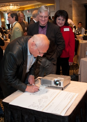 Guests line up to sign a keepsake for Dr. W. Bonham Magness at a surprise reception in his honor earlier this year. Photo by Brian Schnupp.