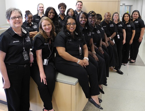 Patient Services employees show off their new look:  black shirts featuring the School of Dentistry logo. Black was chosen via staff survey.