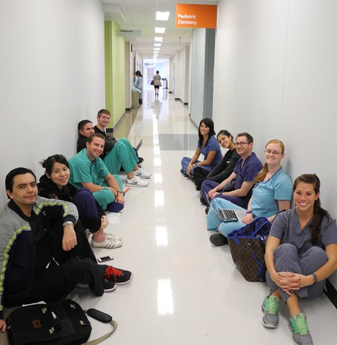 Pediatric dentistry residents wait outside the simulation suite for their turns managing emergencies in the dental chair.  Photo by Rhonda Whitmeyer.
