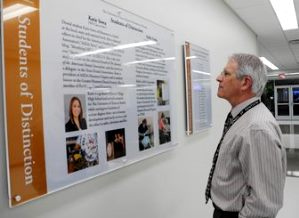 "Associate Dean Phil Pierpont, DDS, reads the new ""Students of Distinction"" exhibit, which was updated Jan. 23."