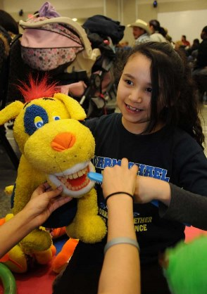An 8-year-old girl holds a puppet while learning to brush its teeth.