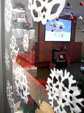 "Photograph of Technology Services decorations, featuring snowflakes on glass, a rotating stack of wrapped presents, a fake fireplace and a projector showing ""Charlie Brown's Christmas"" on the wall."